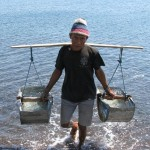 local man carrying sea water to make salt in Amed, Bali