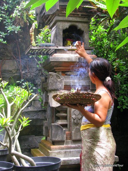 balinese ceremonies-Balinese woman making daily offerings at family shrine